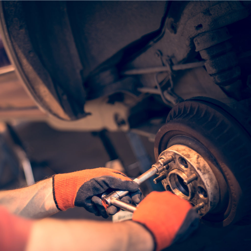 Male mechanic in gloves tightening the nuts using wrench.